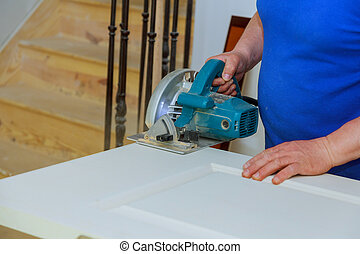 circular saw for cutting wood door the hands of the builder, the man construction and home renovation,