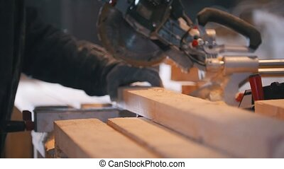 Circular saw sawing a wooden board on joinery, close up