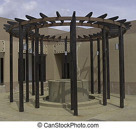 Circular trellis made of wood or timber with water spout and concrete tank in the middle