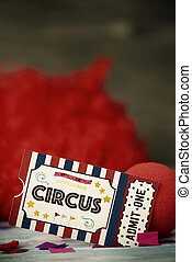 circus admission ticket, clown nose and red wig