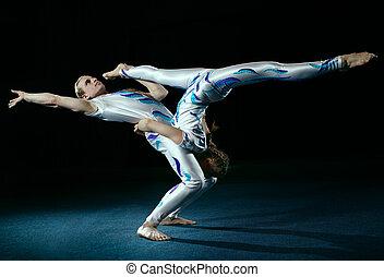 Circus artists perform different tricks. Gym split.