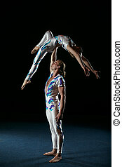 Circus artists perform different tricks. Man holding woman.