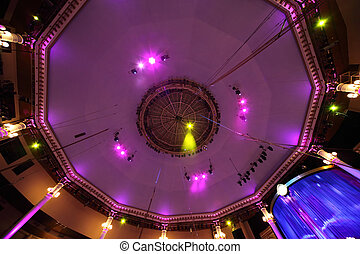 circus interior view on celling with pink light lamps and...