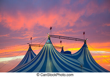 Circus tent in a dramatic sunset sky colorful orange blue...