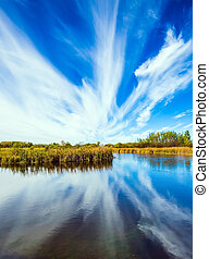 Cirrus clouds are reflected in the Winnipeg River. The ...