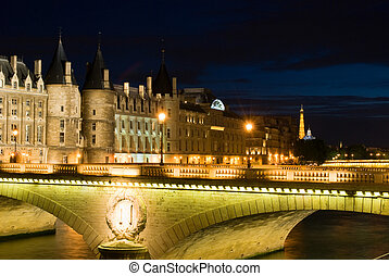 Cite island with Conciergerie and Eiffel Tower. Night view.