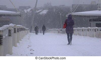 Citizen people walking through urban bridge. Heavy blizzard...