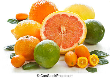 Fresh citrus fruit with leaves on a white garden board.