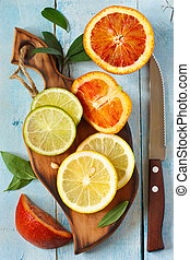 Citrus. - Fresh citrus fruit with leaves on an cutting board...
