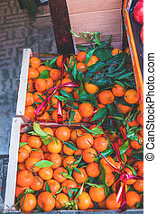 Citrus. Fresh organic Tangerines in a box on display at a farmers market. Ripe oranges. Harvest concept. Top view,