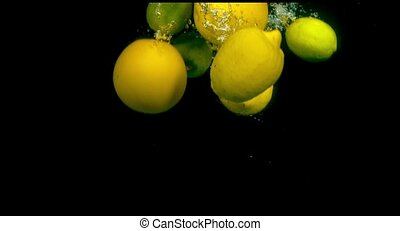 Citrus fruit in water on a black background