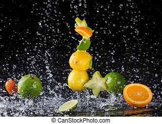 Citrus fruit in water splash on black background - Isolated ...