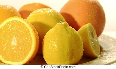 citrus fruit - orange and lemon rotating on a white...