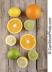 orange, lemon and lime on rustic wood