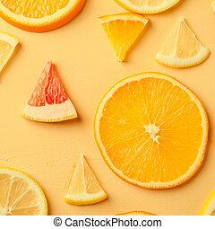 Citrus fruit slices of lemon, orange, grapefruit on yellow background.
