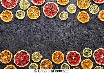 Citrus fruits pattern of lemon, orange and grapefruit on black stone background.