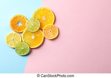 Citrus fruits slices on two tone background, top view