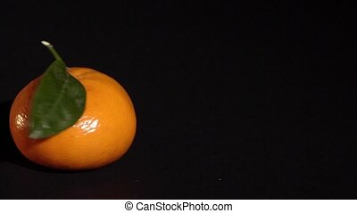 Citrus mandarin with leafes on black background isolated...