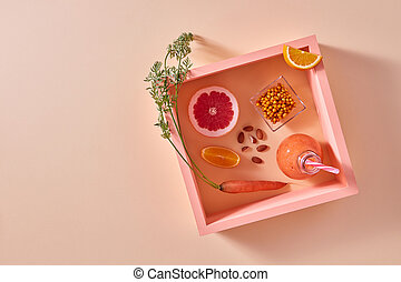 Citrus vegetable smoothies with berries and nuts in a glass on an orange paper background in square frame with copy space. Flat lay.
