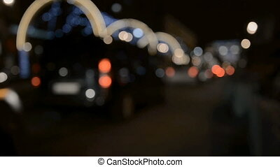 City at night background with cars. Out of focus background with blurry unfocused city lights.