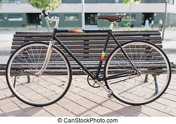 City bicycle fixed gear on wooden seat