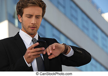City businessman checking his watch and his phone