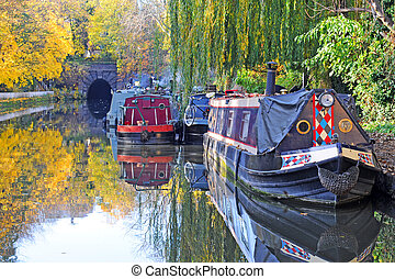 city canal in fall with houseboats and trees, islington, london