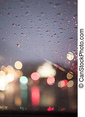 City car lights defocused road street at night in rain