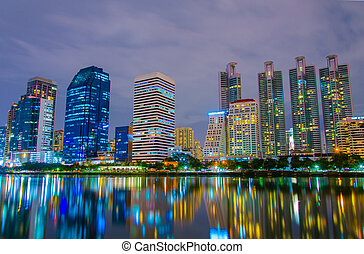 city downtown at night with building reflection in the river Bangkok, Thailand.