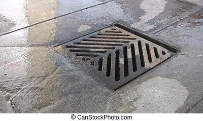 Water running down a city drain.