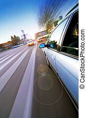 City Driving - A car passing a pedestrian crossing in an...