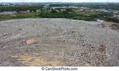 City Dump. The vehicle and people working the garbage. Birds feeding on Food Waste Fly Over It. Aerial View