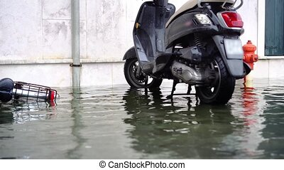 Italian city faces exceptionally high-water level covering street and parking lot with black motorbike against white wall