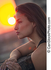 city girl portrait at top of building at sunset