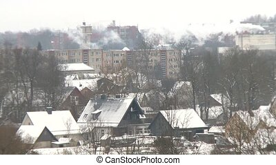 City houses in winter. Smoke rising from building chimney....