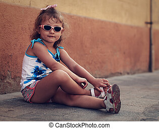 City kid lifestyle. Trendy kid posing in fashion sun glasses