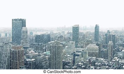 Wide view over city with snow on rooftops in heavy snowfall