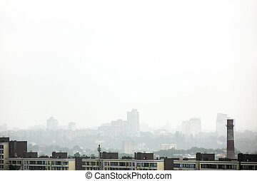City landscape with new houses in the background of a misty cloudy sky.