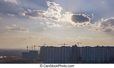 City landscape with new houses under construction on a background of cloudy sky with sunnlight. Aerial view of the drone.