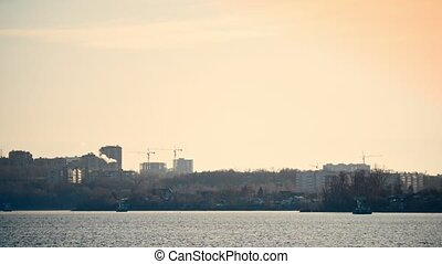 City landscape with river and house under construction at sunset