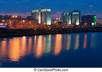 City late in the evening, lights reflected in the river water.
