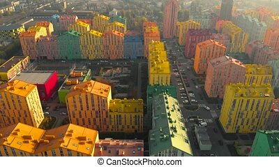 Horizontal aerial view of a residential quarter with streets, cars, pedestrians. City life in a residential quarter with small multi-colored cozy houses. Autumn season. Aerial view, video footage.