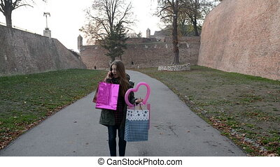 City Life - Attractive woman shopper with paper bags talking...