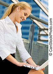 city life - happy businesswoman with laptop computer in the ...
