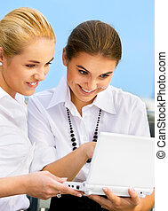 city life - two happy businesswomen with laptop computer...