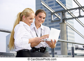city life - two happy businesswomen with laptop computer in ...