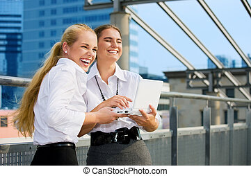 city life - two happy businesswomen with laptop computer in...