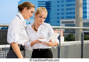 city life - two happy businesswomen with laptop (focus on ...
