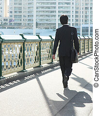 City life - Young white collar worker walking across an ...