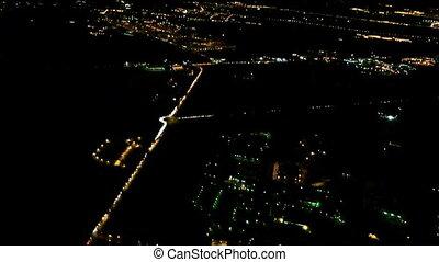 City lights at night from descending aircraft in flight before landing